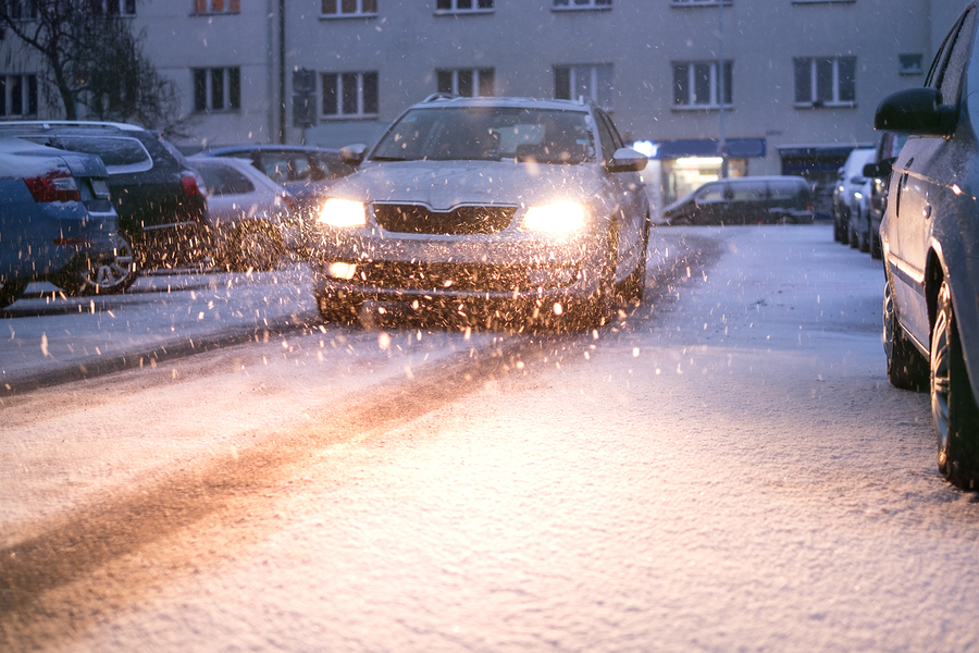Prague city street under the snow. Cars driving on a blizzard road. Snow calamity in the city. Snow covered cars. Winter