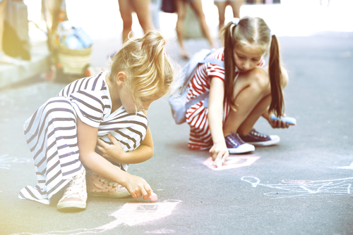 Happy active children drawing with chalk on asphalt